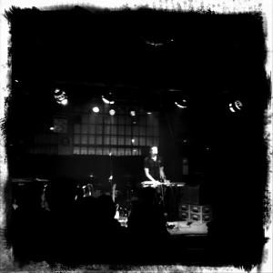 Eine sbstrakte Komposition in Graustufen. Angedeutet: ein singender Keyboarder.